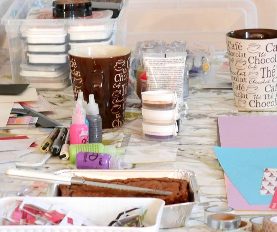 table rempli de matériels créatifs et de tasses de thé
